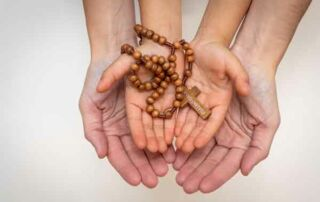 two hands with rosary